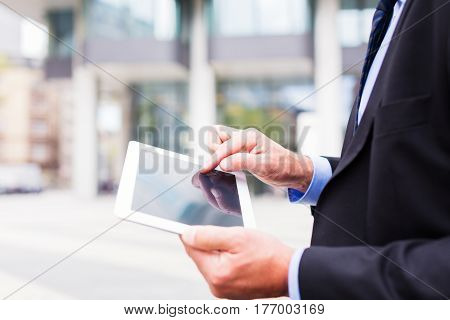 businessman in frankfurt main, checking his email or reading the news on his tablet