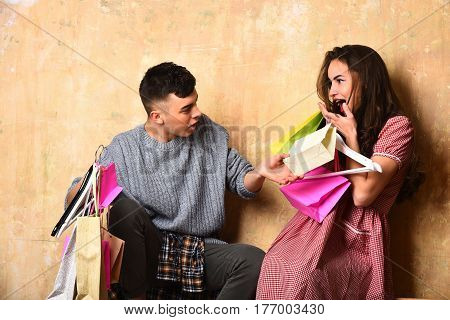 surprised happy couple of pretty sexy girl or cute fashionable woman with long brunette curly hair and young guy or handsome man holds hangers colorful shopping bags or packages on beige background