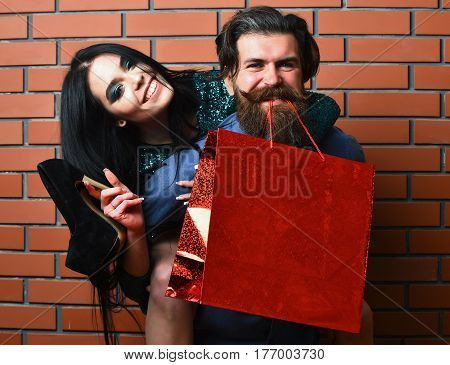 happy couple of bearded man long beard brutal caucasian hipster with moustache and pretty woman or sexy girl with brunette hair makeup in green sequins dress hold shopping bag shoes on brick wall