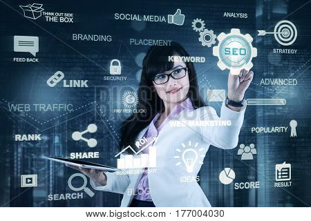 Young businesswoman holding a digital tablet and pressing SEO button on a virtual screen. SEO concept