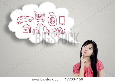 Young businesswoman thinks her dream while looking at cloud speech