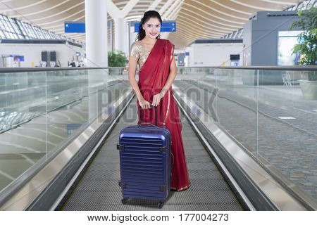 Pretty Indian woman holding a bag and wearing saree clothes on the escalator in international airport