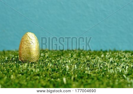 An easter egg wrapped in golden paper displayed on artificial grass and a blue background