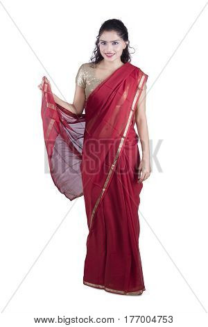Photo of a young Indian woman standing in the studio while wearing a red saree. Isolated on white background