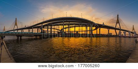 Sunset scence of Bangkok Panorama View of Bhumibol suspension bridge in Bangkok city with sunset sky and clouds at Bangkok Thailand. And Reflection on river. Photographer is taking photo