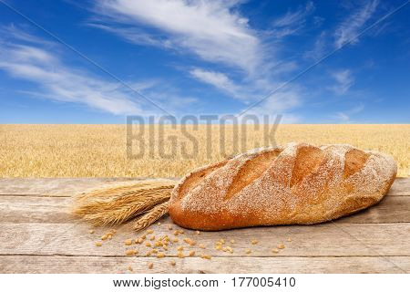 long loaf on wooden table with golden field on the background. Fresh baked traditional bread on nature background