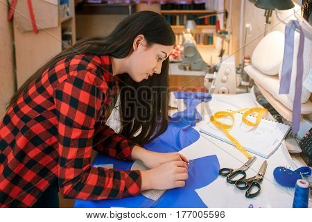 young woman seamstress making pattern on fabric with tailors chalk. Girl working with a sewing pattern. Hobby sewing as a small business concept. Tailor measuring textile material