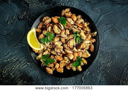 Seafood. Steamed Musseles appetizer with sprinkle of parsley and lemon juce served on black plate
