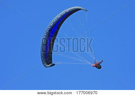 Paraglider fling under his wing in a blue sky