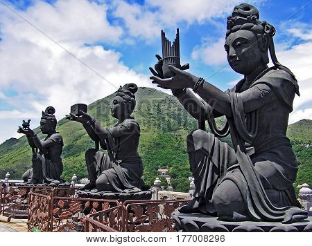 Buddhist statues in Ngong Ping on the island of Lantau in Hong Kong, praising and making offerings to the Tian Tan Buddha