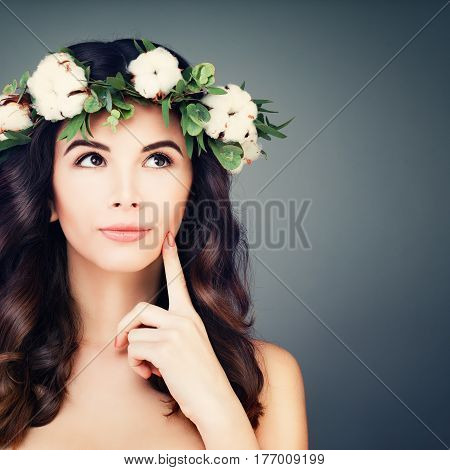 Perfect Brunette Woman with Healthy Skin and Hair Looking Up. Flowers Wreath Spring Makeup Curly Hairstyle on Blue Background. Young Spa Model with Wavy Hair