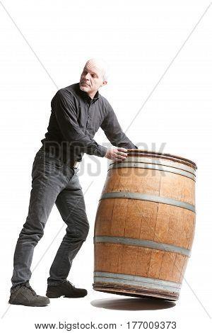 Middle-aged Man Tilting A Wooden Cask Or Barrel