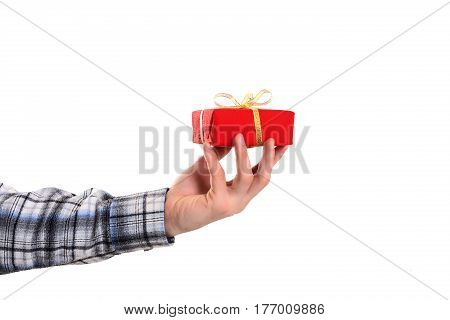 Hand of casual dressed Man holding small decorated Christmas Gift in red Paper with golden Ribbon on white Background