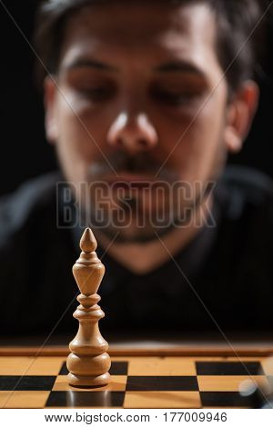 Portrait of adult man who is participating in chess game and thinking about capitulation.