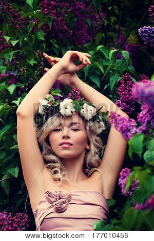 Spring Model Girl with Prom Hairstyle Outdoors. Glamour Woman with Blonde Wavy Hair on Flowers Background