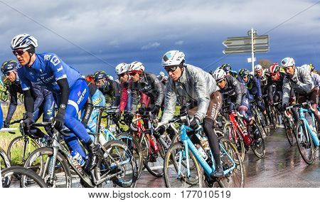 Cernay-la-Ville France - March 5 2017: Alberto Contador of Trek Segafredo Team surrounded by other big favourites inside the peloton riding on a wet road during the first stage of Paris-Nice on 5 March 2017.