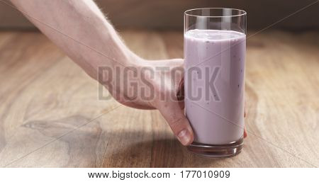 man hand bring blueberry yogurt in glass on wood table, 4k photo