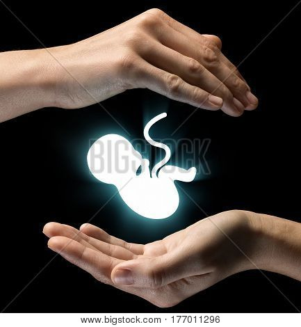 Isolated image of two hands on black background. Baby icon in the center as a symbol of caring for baby and mother. Concept of caring for baby.