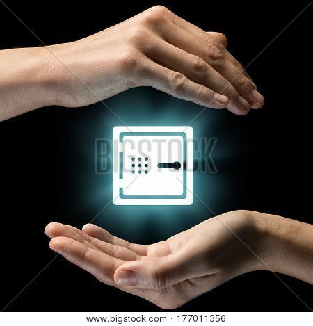 Isolated image of two hands on black background. Safe icon in the center as a symbol of protection of cash deposits savings. Concept of protection of cash deposits savings.