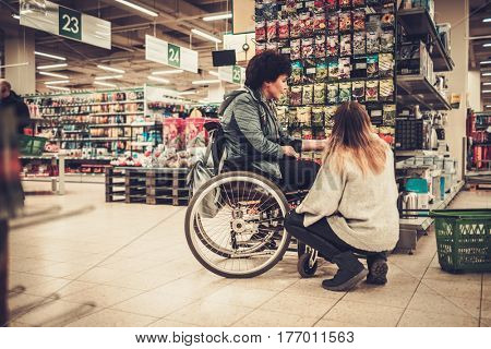 Young girl helping her disabled mothter in wheelchair in a department store.