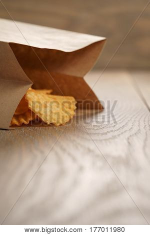 rippled potato chips with paprika in paper bag, with copy space