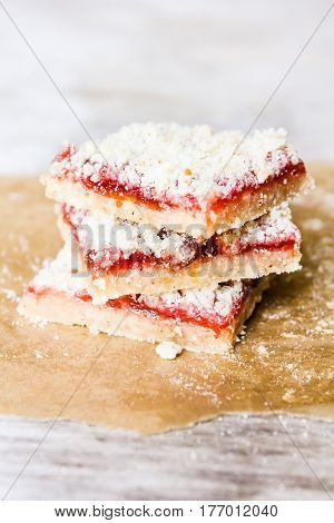 Stack of cake or cookies with plum, strawberry, raspberry and cherry jam or marmalade with sweet crumbs, cinnamon and nuts on a parchment paper, selective focus