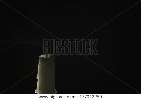 tall candle with smoke trail over black background, simple photo
