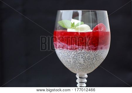 Pudding From Chia Seeds And Raspberries With Cottage With Mint In Glass On Black Background