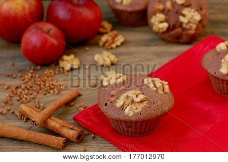 Gluten Free Muffins From Buckwheat Flour, Apple, Cinnamon And Walnuts On Red Cloth On Brown Wooden T