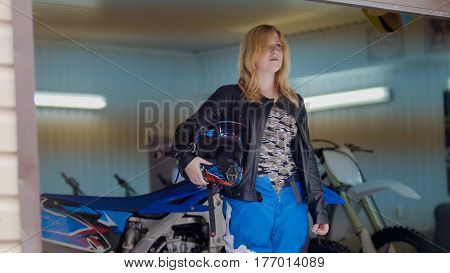 Woman MXgirl with motocross helmet in the garage, telephoto