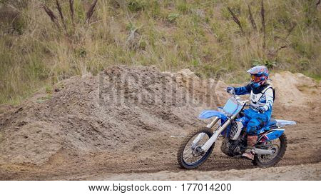 Motocross racer on dirt bike at sport track, telephoto