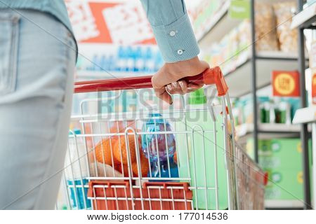Woman doing grocery shopping at the supermarket she is pushing a full shopping cart hand close up lifestyle and retail concept