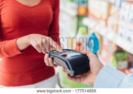Woman at the supermarket checkout she is entering the security pin on the terminal shopping and retail concept