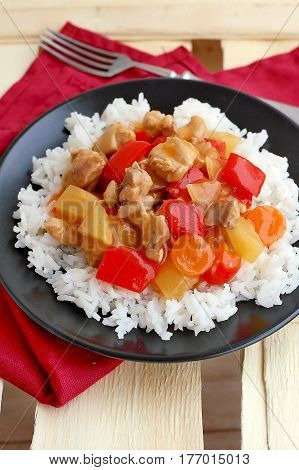 Sweet And Sour Food With Rice,red Pepper,pineapple,onion And Chicken Meat On Red Cloth On Black Plat