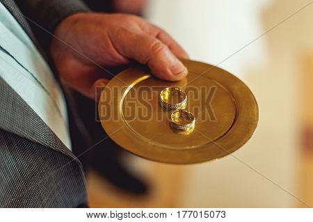 Classic gold wedding ring on a gold plate at church in hands of sexton