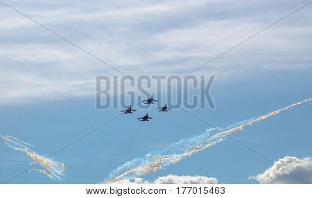 Flight groups of four fighter jets at an air show on a blue sky background, clouds, and thermal rocket plumes.