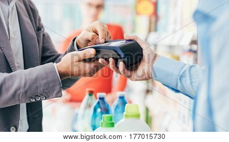 Man doing grocery shopping at the supermarket and paying with a credit card at the checkout he is entering the security pin on the terminal