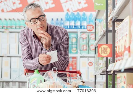 Man doing grocery shopping at the supermarket he is pushing a cart and checking a list