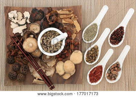 Traditional chinese herbal medicine selection on a maple wood board with chopsticks and mortar with pestle and in china spoons on bamboo background.