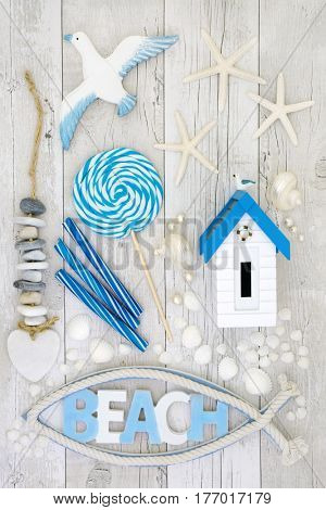 Beach art abstract design with seashells and pearls, rock candy, heart shaped rock mobile and decorative seaside objetcs on distressed white wood background.