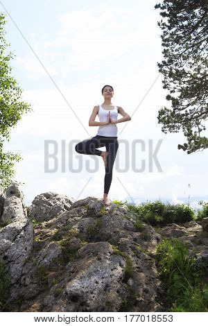 Attractive young woman doing a yoga pose for balance and stretching staying on top of high rock in the mountains sunny day blue sky with clouds