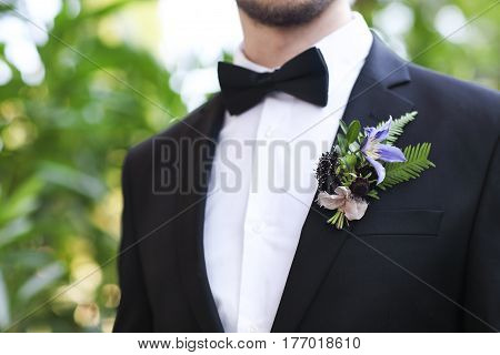 Gentle groom boutonniere with roses chrysanthemum and beads