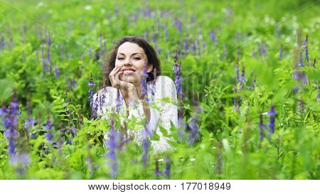 Happy pretty brunette woman in flower field cute female relaxed on flowers meadow spring nature having fun outdoor