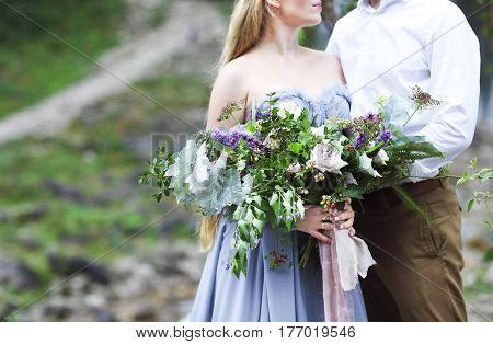 Wedding couple groom and bride with bouquet posing on sunset. Close up