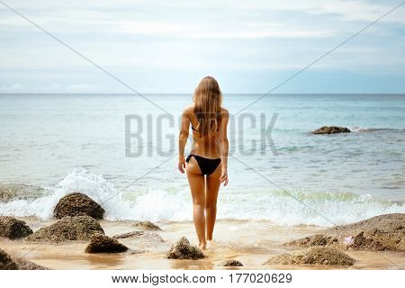 Outdoor portrait of young elegant fit woman standing backwards and going into sea to swim in waves near tropical beach with rocks. Sports girl in bikini enjoy nature paradise summer vacation, Thailand