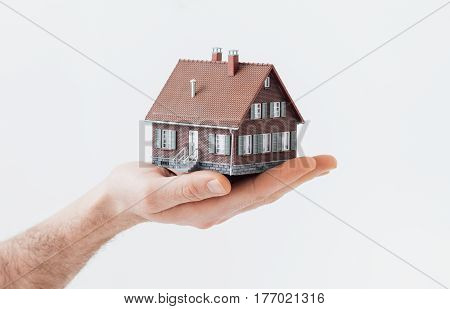 Man holding a model house: real estate insurance and home loan concept
