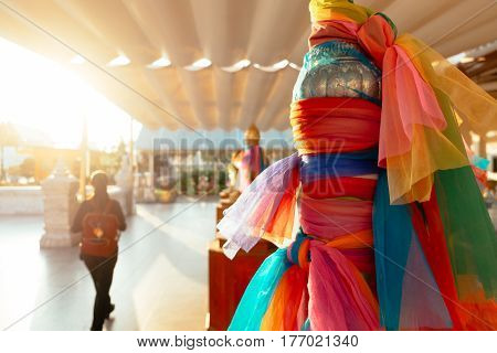 Belief in worship in sacred Buddhist temple with satin colorful ribbons at beautiful sunset light, Bangkok, Thailand