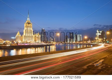 Blurred night traffic movement lights at the center of Moscow, aerial urban view with Stalin Skyscraper and its reflection in the Moscow River, outdoor travel background