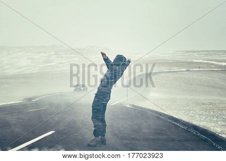 Woman Tries To Stand Against Snow Flurry Seen Through A Windshield.