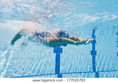 Backstroke swimming start, underwater shoot, blue background